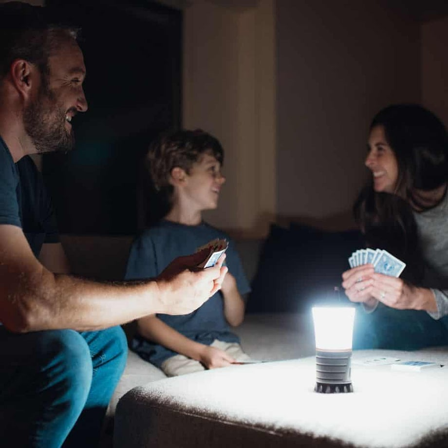 family playing cards in the dark using lantern
