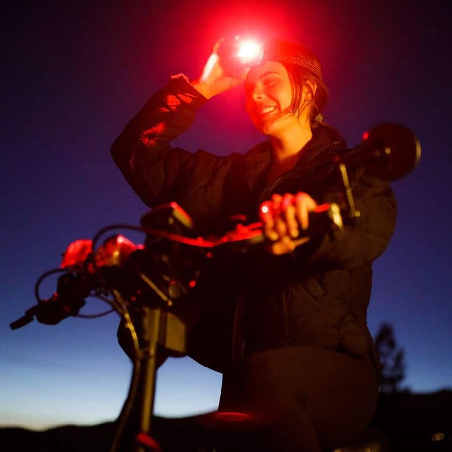 Woman on bike wearing headlamp in red mode