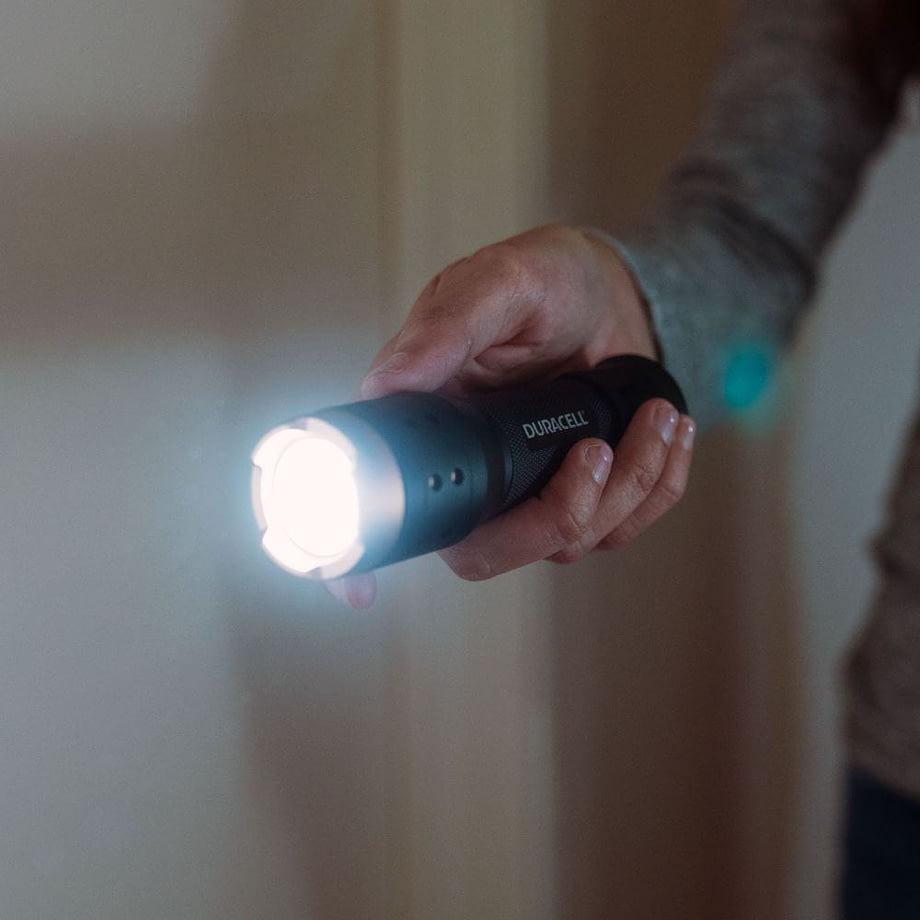 man holding flashlight in a dark home