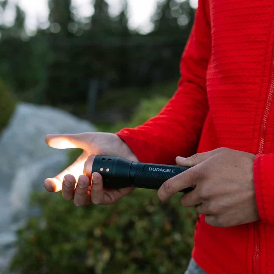 Man shining flashlight into hand